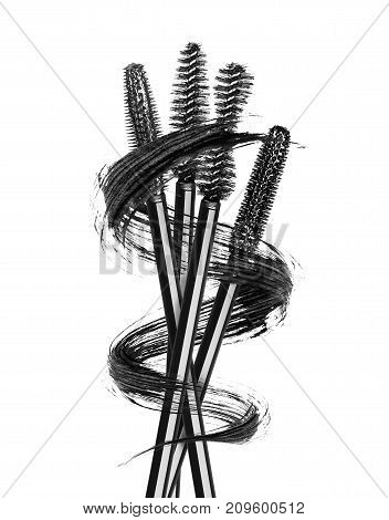 Various mascara brushes wrapped in a smear in the shape of a spiral isolated on white background