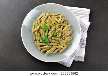 Pasta with homemade pesto sauce in a gray plate on a dark stone background top view copy space. Fresh summer food