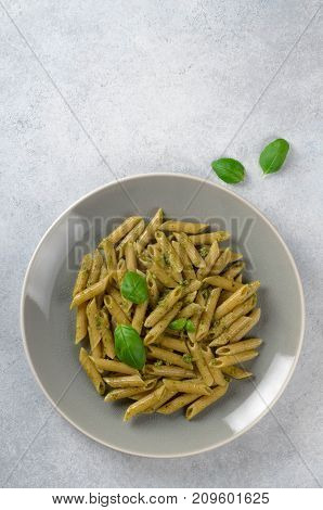 Pasta with homemade pesto sauce in a white plate on a light-blue stone background vertical image top view copy space. Fresh summer food