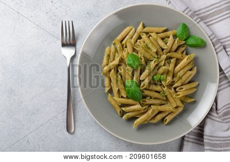 Pasta with homemade pesto sauce in a white plate on a light-blue stone background top view copy space. Fresh summer food