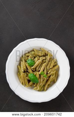 Pasta with homemade pesto sauce in a white plate on a dark stone background vertical image top view copy space. Fresh summer food