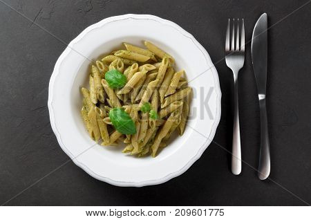 Pasta with homemade pesto sauce in a white plate on a dark stone background top view copy space. Fresh summer food