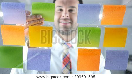Man Working On Sticky Notes Attached On Glass In Office