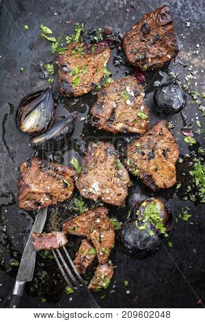 Barbecue t-bone lamb steak with carbonized onion and seasonings as top view on a rusty board