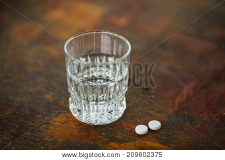 Glass of pure water and few white round pills on the wooden table. Medical tablets
