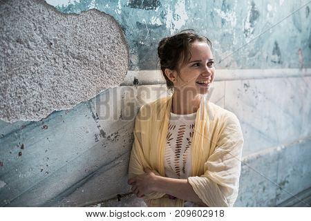 smiling girl standing on old wall background
