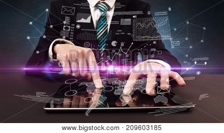 Businessman in formal attire typing with financial concept around