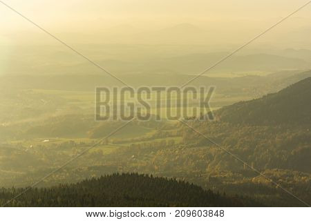 Hot yellow sky during sunset. Nature with green grass and branches with sunshine. Big stones background. Moss on the rock. Mineralogy. Sunset purple blue sky over foggy forest landscape.