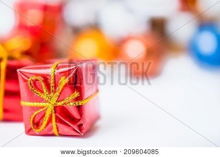Close-up of red xmas gifts with blurred colorful balls and Christmas decor in background. Christmas and New Year concept with copy space. Christmas greeting card.