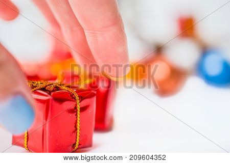 Close-up of women hand take a red xmas gift with blurred colorful balls and Christmas decor in background. Christmas and New Year concept with copy space. Christmas greeting card.