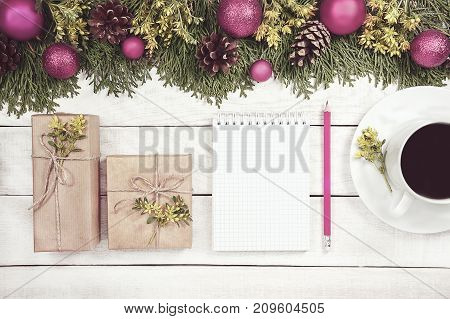 Christmas background with xmas tree red ornaments and on the white wood. Magic deer and gift wrapped craft paper ande decored flower. Top view. Lovely picture for wallpaper. Modern floral garland