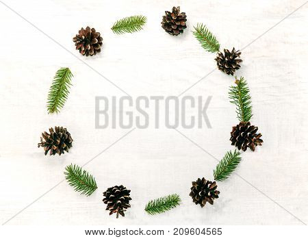 Christmas wreath made of pine cones and sprigs fir on the white wooden background. Natural decor ornament for holiday card. Xmas card. Happy New Year. Top view