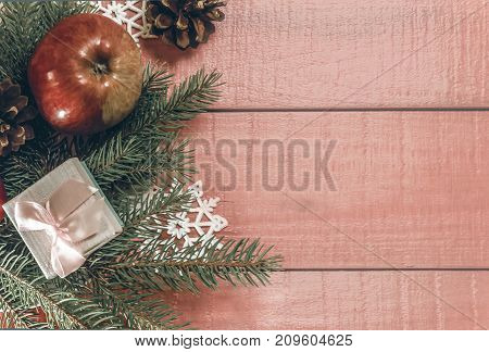 Christmas holiday decor. Frame decorated gold balls fir branches and copy space. Xmas card made rustic style in creative concept. Modern ornament on the pink wooden background