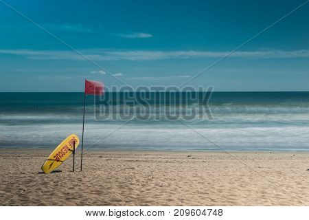Kuta beach, bali, indonesia. Surf rescue point. Yellow rescue surfboard and red flag