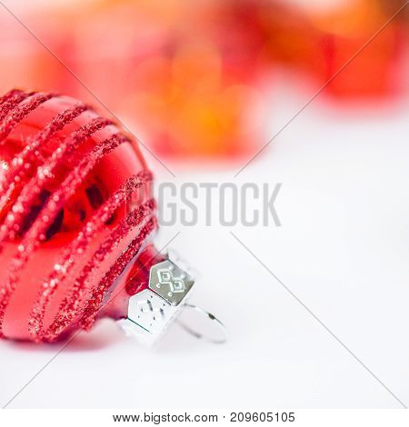 Close-up of xmas red ball with blurred colorful Christmas decor in background. Christmas and New Year concept with copy space. Christmas greeting card.