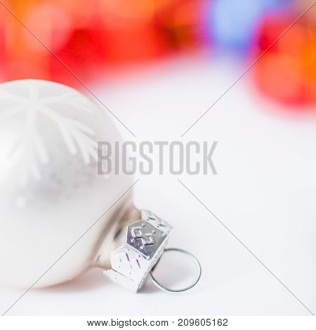 Close-up of xmas white ball with blurred colorful Christmas decor in background. Christmas and New Year concept with copy space. Christmas greeting card.
