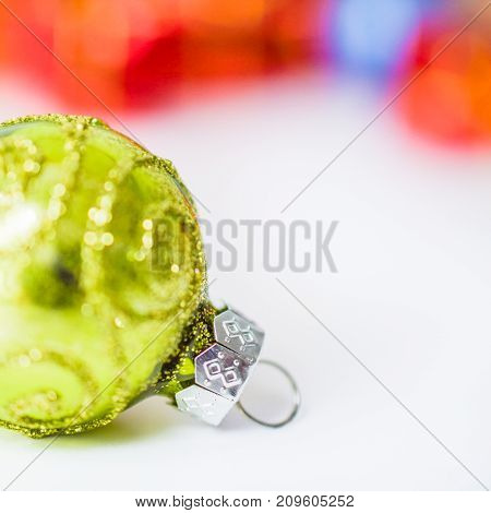 Close-up of xmas green ball with blurred colorful Christmas decor in background. Christmas and New Year concept with copy space. Christmas greeting card.