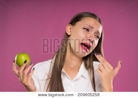 upset girl on a pink background holds an apple