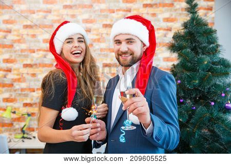 Confident bearded man in a Santa cap and worgeous woman with a glass and bengal lights celebrating Christmas on a blurred festive background.