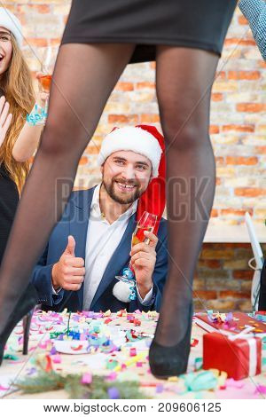 Close-up picture of long, beautiful woman's legs standing on the table and happy man in santa cap on a festive Christmas background.