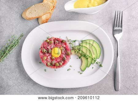 Delicious steak tartare with yolk and capers on plate