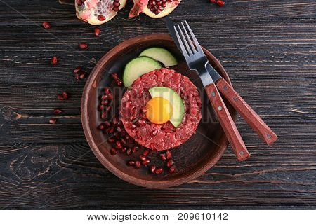 Delicious steak tartare with yolk, avocado and pomegranate seeds on plate