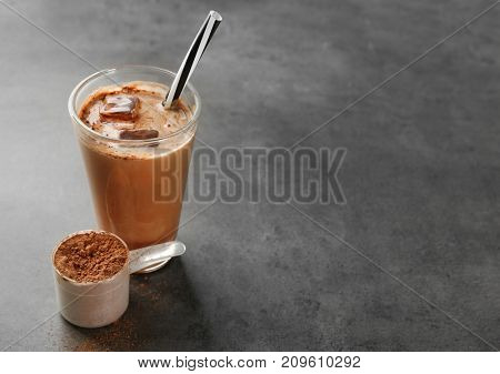 Glass with protein shake and powder in scoop on table
