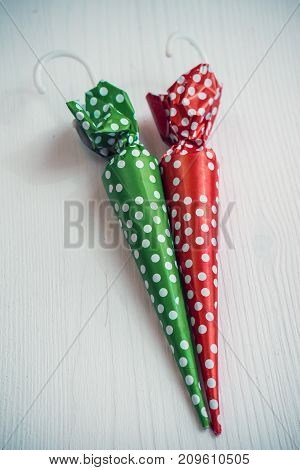 Sweet christmas background. Red and green candies in shape of umbrella on white wood. Xmas and other winter holidays concept with copy space, top view, toned