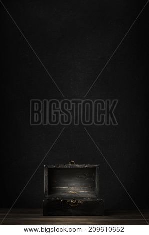 A dark wooden treasure chest with lid open and lit on planked surface with black chalkboard background.