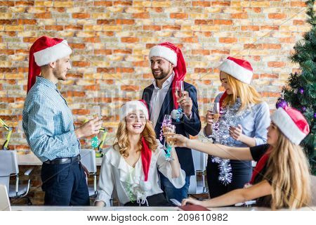 New Year's corporate in a friendly team in a working office with a glass of champagne and New Year's attributes