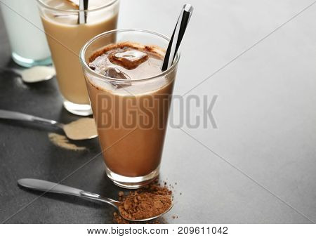 Glasses with different protein shakes and powders in spoons on table