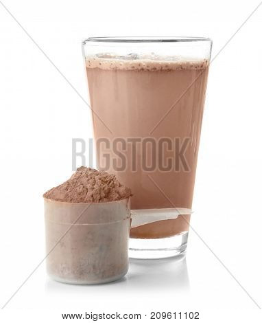 Glass with protein shake and powder in scoop on white background
