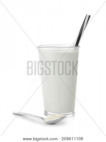 Glass with protein shake and powder in spoon on white background