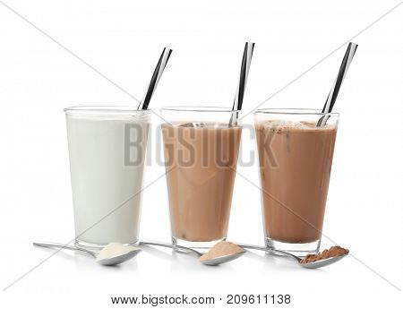 Glasses with different protein shakes and powders in spoons on white background