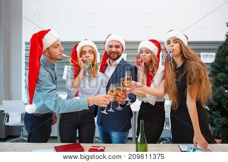 Group of funny, beautiful office people in red Santa hats on a Christmas night with alcoholic drinks on a blurred festive background.