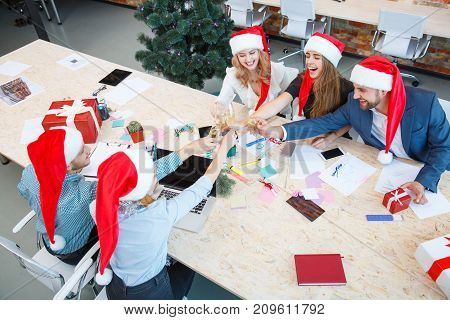 Fantastic group of festive business co-workers clinking glasses of champagne at the Christmas party on a blurred office background.