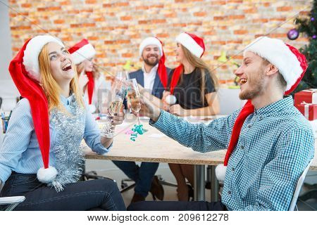 Successful business company drinking alcohol and celebrating the new year on a blurred office background. Friends toasting wine on Christmas.