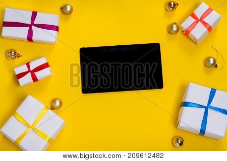 top view of a box with gifts in white wrapping paper with a tablet, an iPhone in the center on a yellow background.