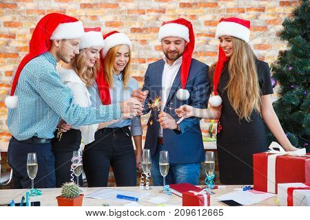 Joyful, festive people lighting up Christmas sparklers on a blurred background. Group of friends in Santa hats having fun with bengal lights.