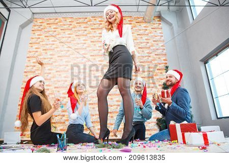 Drunk group of office people in Christmas caps drinking and pretty woman standing on table with a glass of wine on a festive background. Copy space.