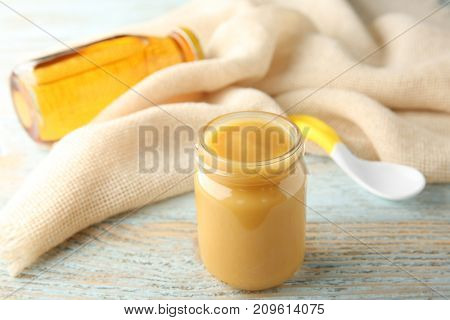 Jar of tasty baby food on wooden table