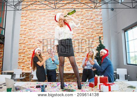 Attractive young girl in a Christmas santa hat dancing on the table with a bottle of champagne with her office colleagues on a festive background.