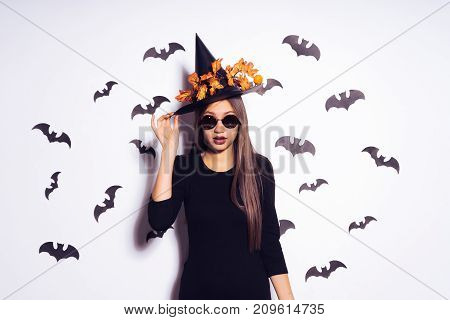 cheerful girl is going to a Halloween party. Witch dress, autumn orange leaves on a black hat
