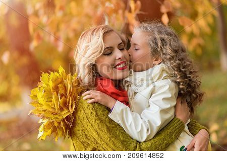 A portrait of a happy family : a young beautiful woman with her cute daughter. Young daughter hugs mother in autumn outdoor. Fashion family concept