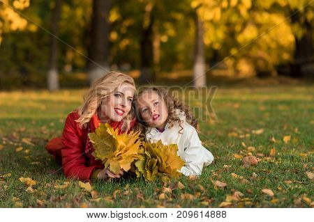 Portrait of smiling mother and daughter with leaves in hands lying on yellow grass. Beautiful family resting in the park. Autumn portrait.