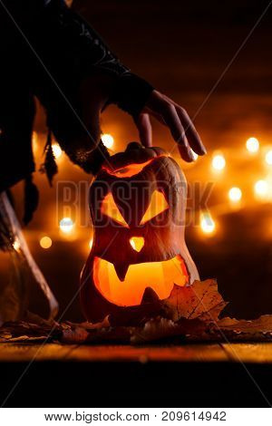 Photo of halloween pumpkin cut in shape of face with witch's hand on background with burning yellow lights