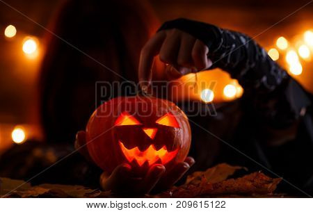 Picture of witch with long hair showing hand on halloween pumpkin on background with burning garlands
