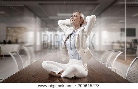 Business lady meditating at work. Mixed media