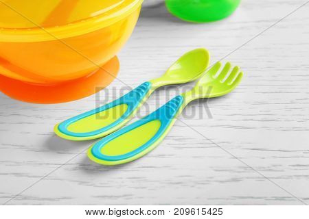Colorful plastic eating utensils for baby on table