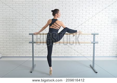 Ballerina stretches herself near barre at ballet studio, full length portrait